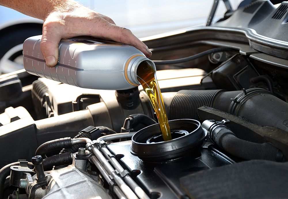 Hombre cambiando el aceite de su coche