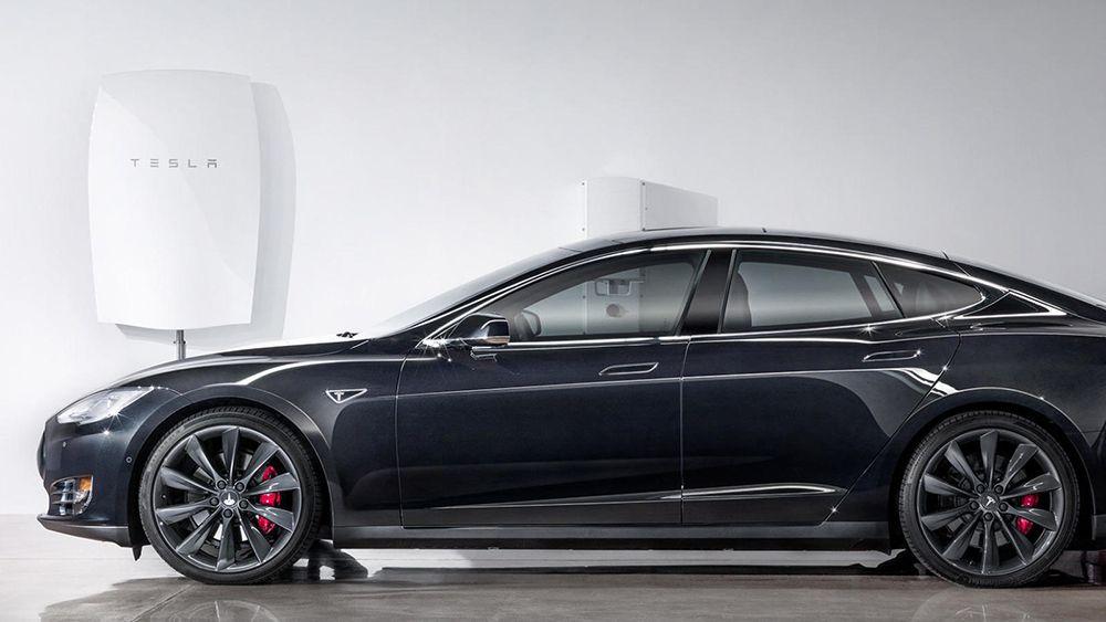 Perspectiva lateral de un Tesla Model X con cargadores Tesla detrás