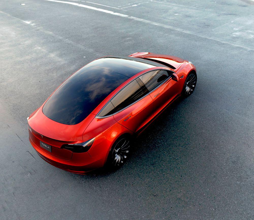 Perspectiva aérea trasera y lateral del Tesla Model 3 de color rojo